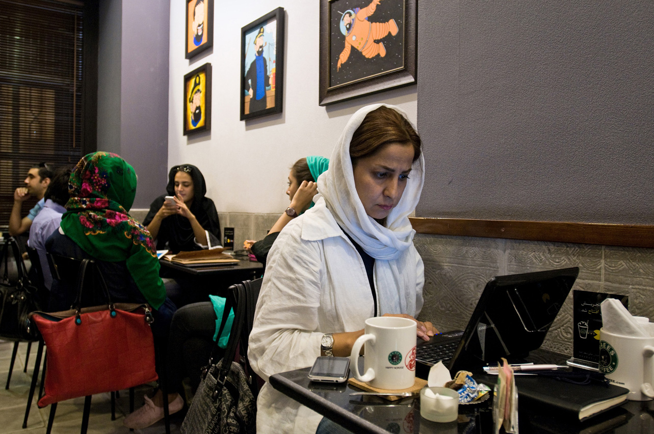 "Ladan, works while enjoying the ambience in Cafe Raees in Tehran. The Cafe Raees is quite affected by ""Starbucks"". Bootleg franchise joints have been popping up in urban Iran one after another in recent years."