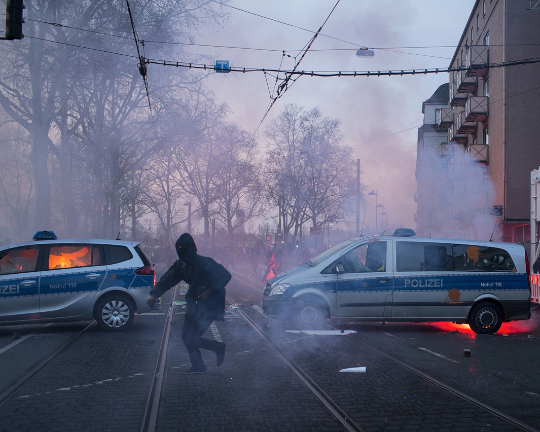 Violent protesters attack police cars and burn the left one on the picture about 500m from the new headquarters of the European Central Bank.