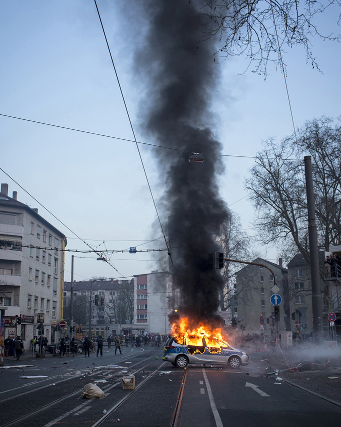 A police car burns down after it was attacked by violent protesters.