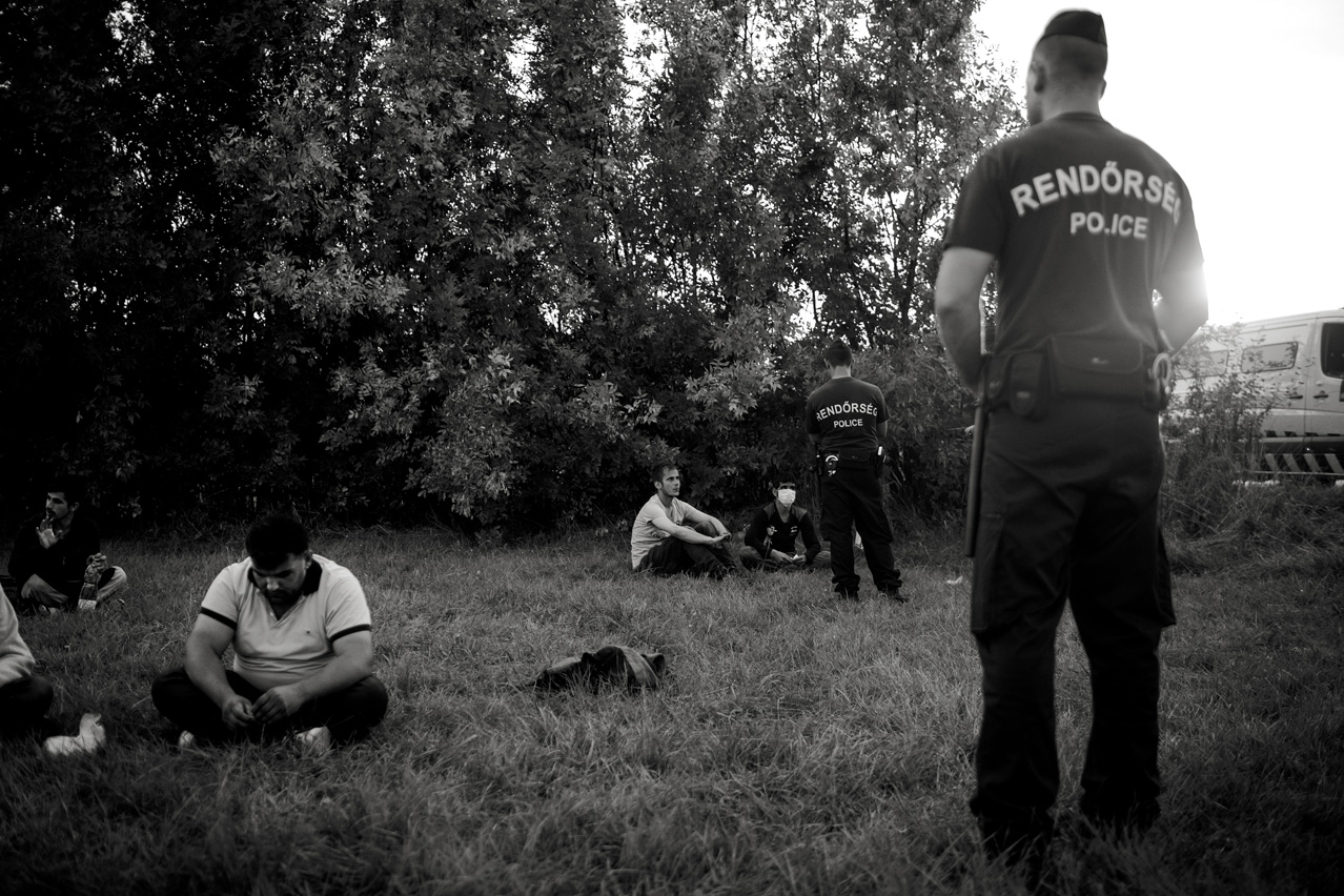 Refugees from Afghanistan arrested by Hungarian police rest on the lawn.