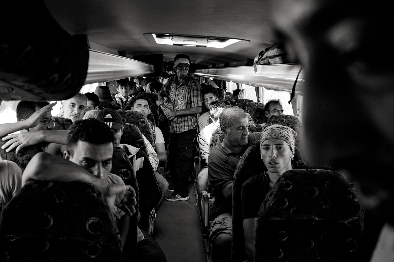 Refugees install themselves in a bus picking them up at the Horgos-Röszke border crossing as they board it to take them to the Croatian border.