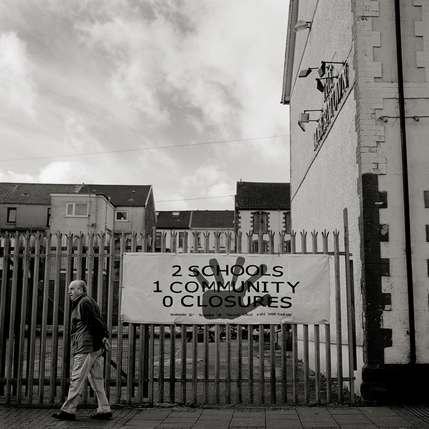 "An elderly man passes a sign which reads ""2 schools, 1 community, 0 closures"" in Ynysybwl, Wales as a campaign against the planned closure of one of the schools in the community. Ynysybwl, once home to the large Lady Windsor Colliery, which was closed down in 1988 was hit by the recession. ""Young people leave for the cities, retired people come back to leave silent and next to the nature"" says Wayne Cadwallader, a former miner from the town."