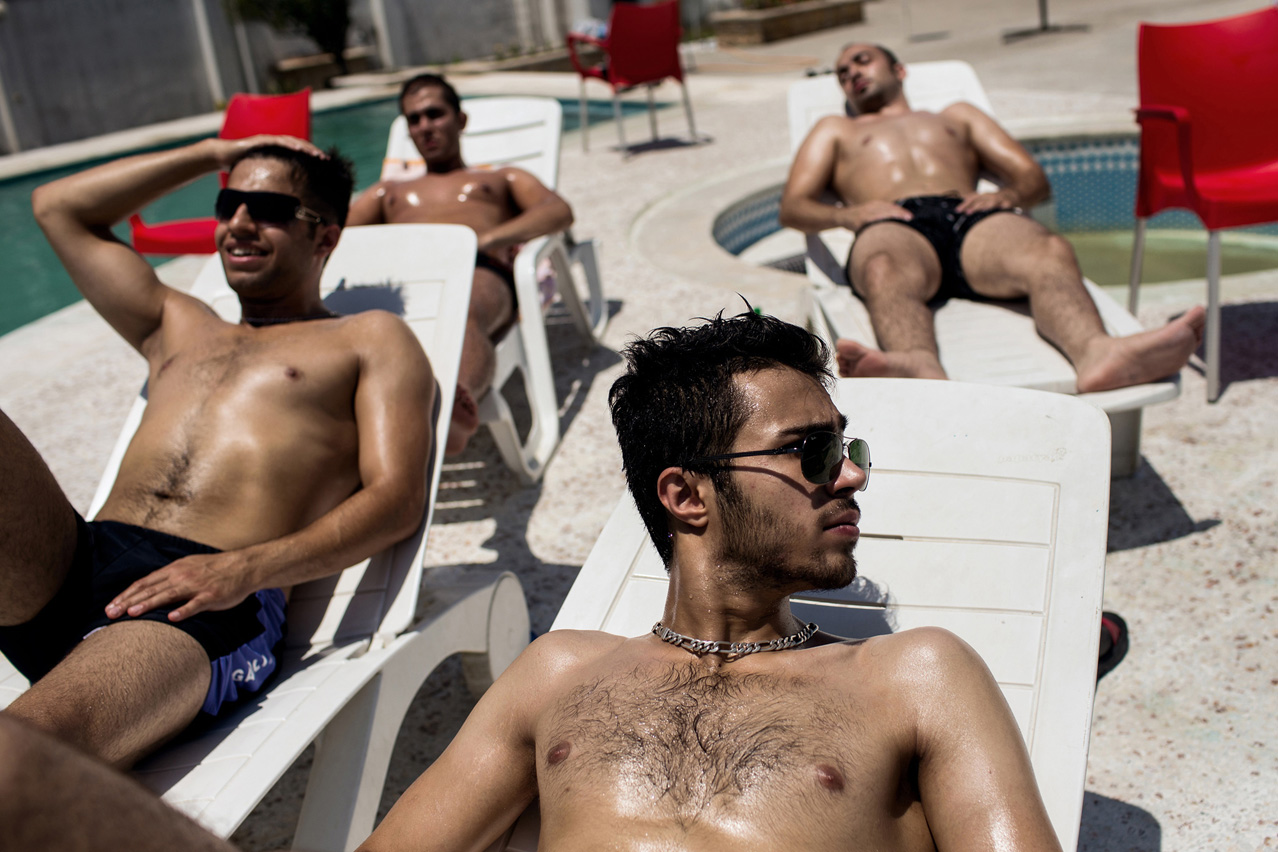 A group of young men takes sun bath in a private complex in Northern Iran. Although Islamic morals are taken laxly in private areas in Northern Iran, gender segregation in the swimming pool is still strictly controlled.