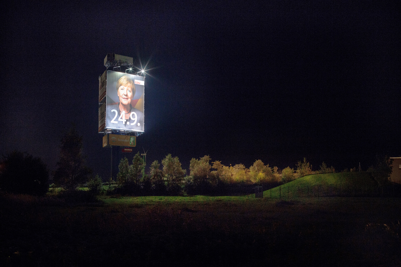 2017. A giant election campaign poster of Angela Merkel lits the surroundings of the A9 motorway in central Germany.