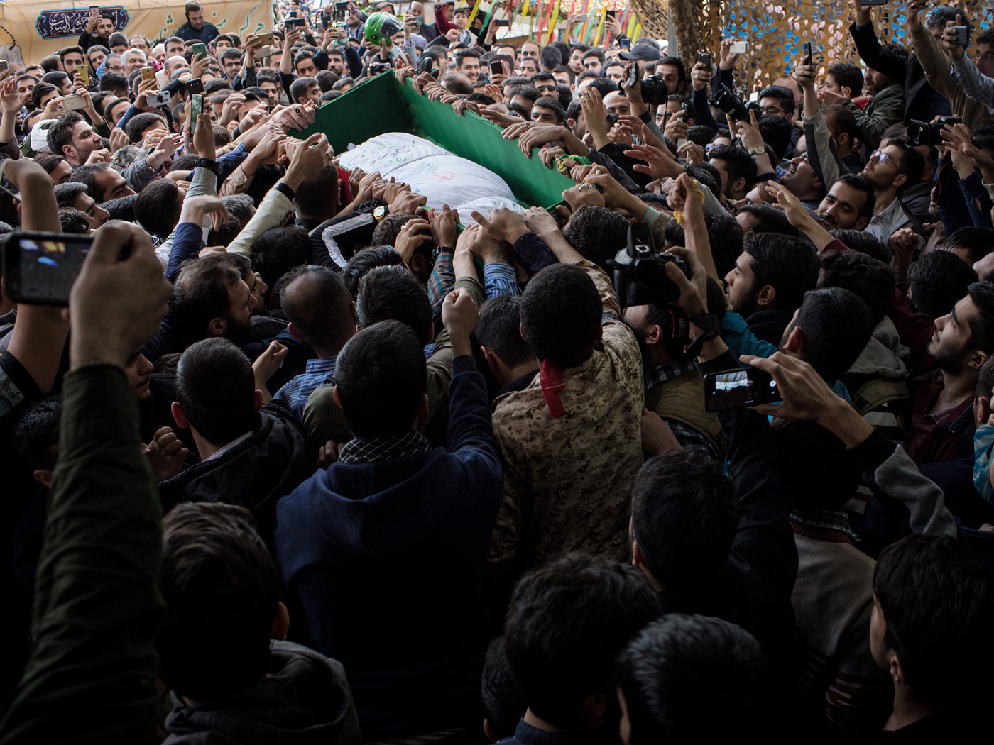 Mourners try to reach the coffin carrying the corpse of Majid Ghorbankhani who died 3 years earlier in Khan Tuman during the Syrian conflict to earn blessings. The corpse has been identified through its DNA and was handed over to the family of the martyr prior to a public farewell ceremony.
