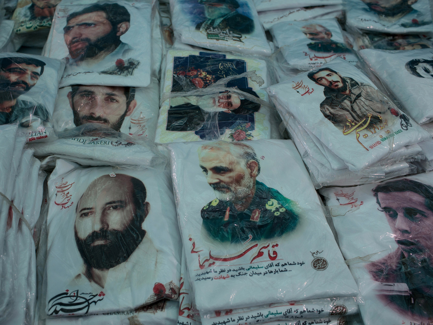 "Stacks of T-shirts printed with portraits of prominent martyrs from different generations Ali Sayyad Shirazi, Mehdi Bakeri, Mostafa Chamran, Ghassem Soleimani, Hassan Bagheri and Ebrahim Hadi, lay out for sale around ones depicting the Supreme leader of the Islamic Republic, Ayatollah Ali Khamenei in a market at the Martyrs' Memorial. Martyr related merchandise in ""Che Guevara style"" is an important industry addressing a pious clientele across the Shiite Middle East."