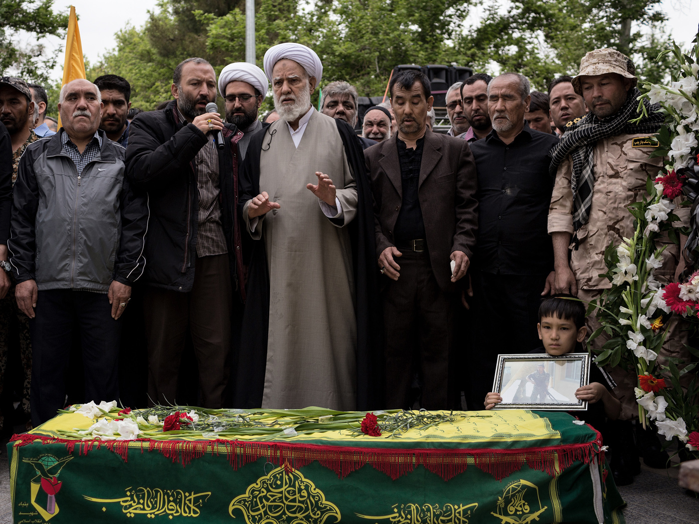 Volunteers pray to the corpse of Alireza Akbari after carrying it through the Fallah neighbourhood of Tehran on Thursday April 18th, 2019 in celebration and mourning of his martyrdom. Alireza Akbari died in Syria four years earlier serving the Fatemioun brigade which is a military unit connected to the Islamic Revolutionary Guards in which Afghan citizens serve. Many of its members are refugees residing in Iran. It has been active in the Syrian conflict over the past years.