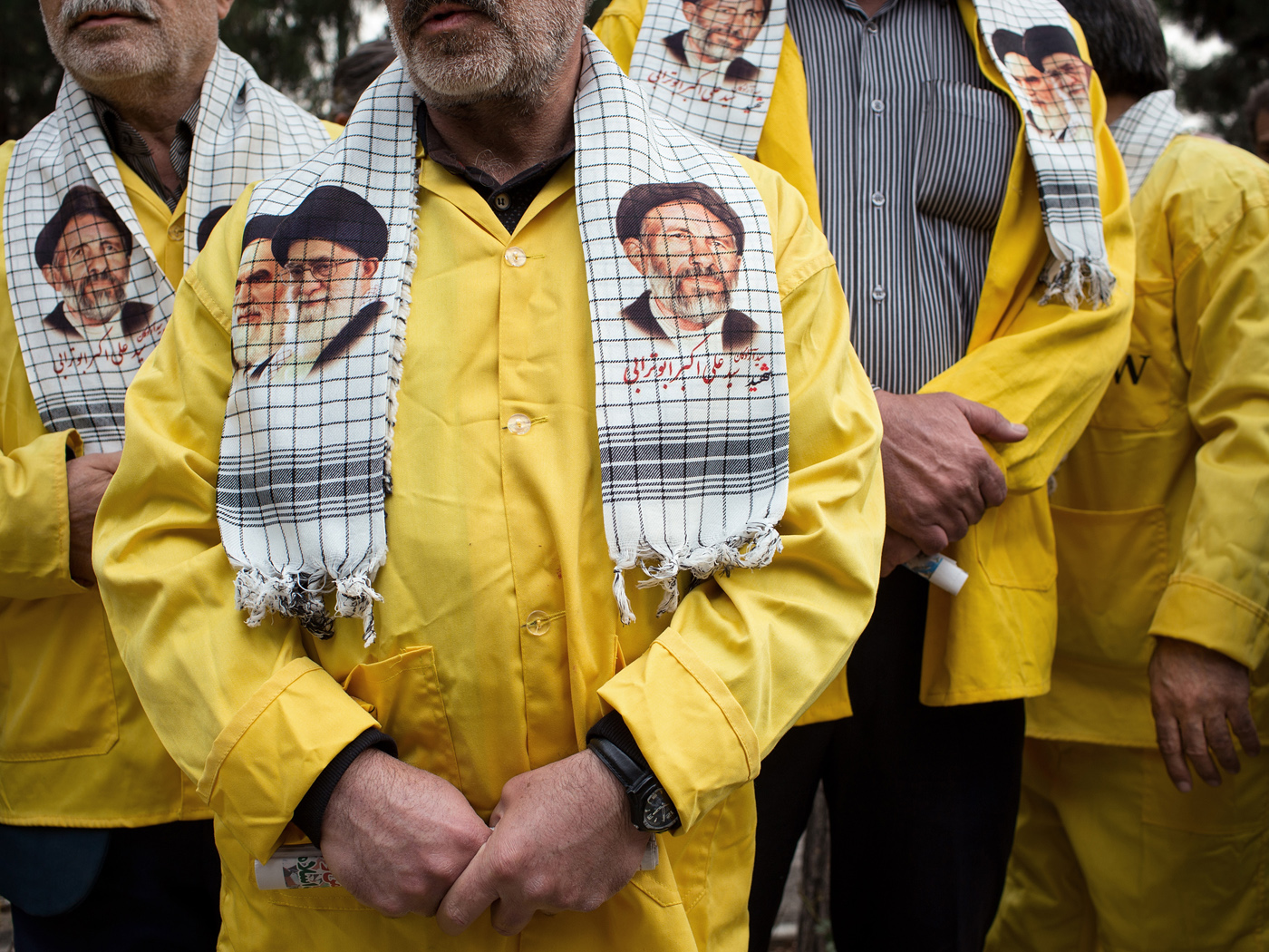 Former prisoners of the Gulf War wearing yellow prison overalls during pray for their dead comrades at Tehran's central cemetery (Behesht-e Zahra).