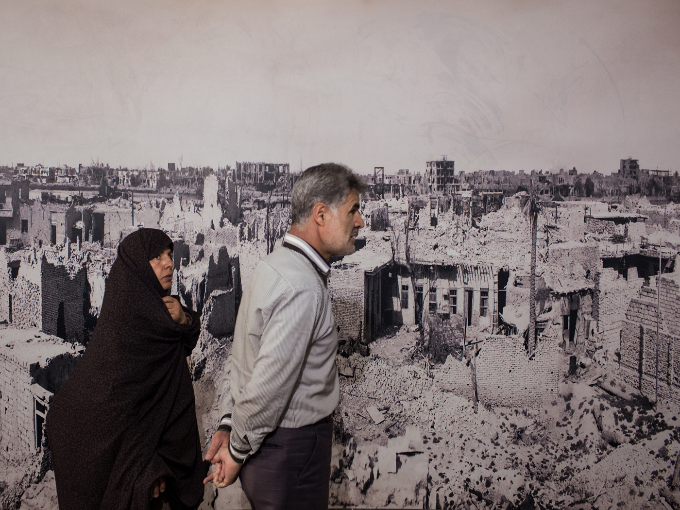 Visitors of the Holy Defense Museum pass by a panorama of Khorramshahr destructed by the Gulf War.