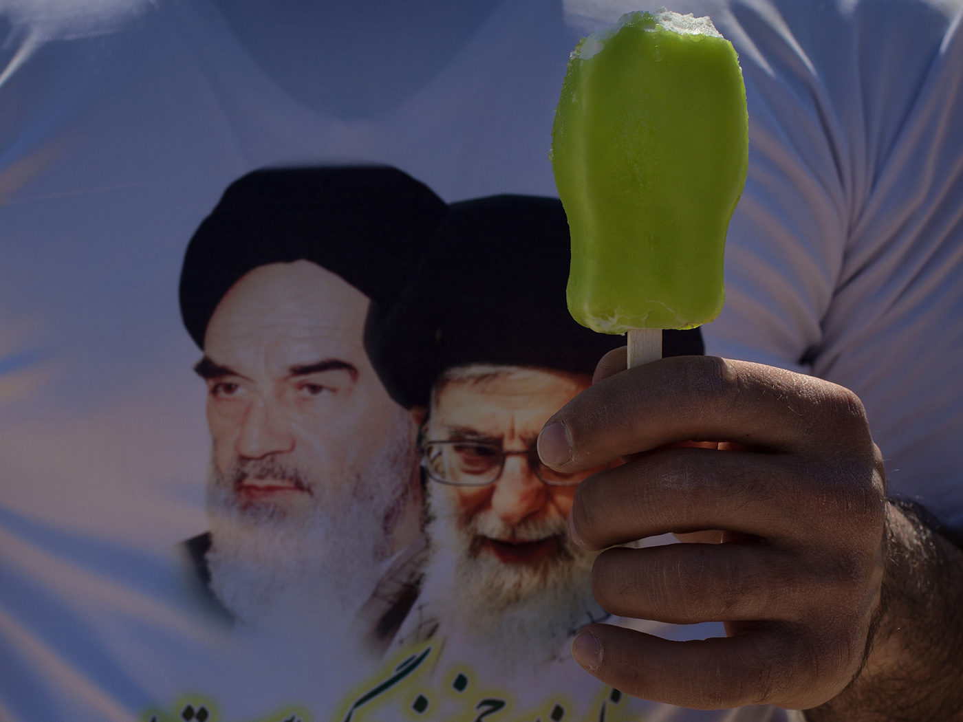 A visitor wears a t-shirt depicting the deceased and the current leaders of the Islamic Republic.
